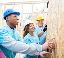 Community volunteers work together to build homes.