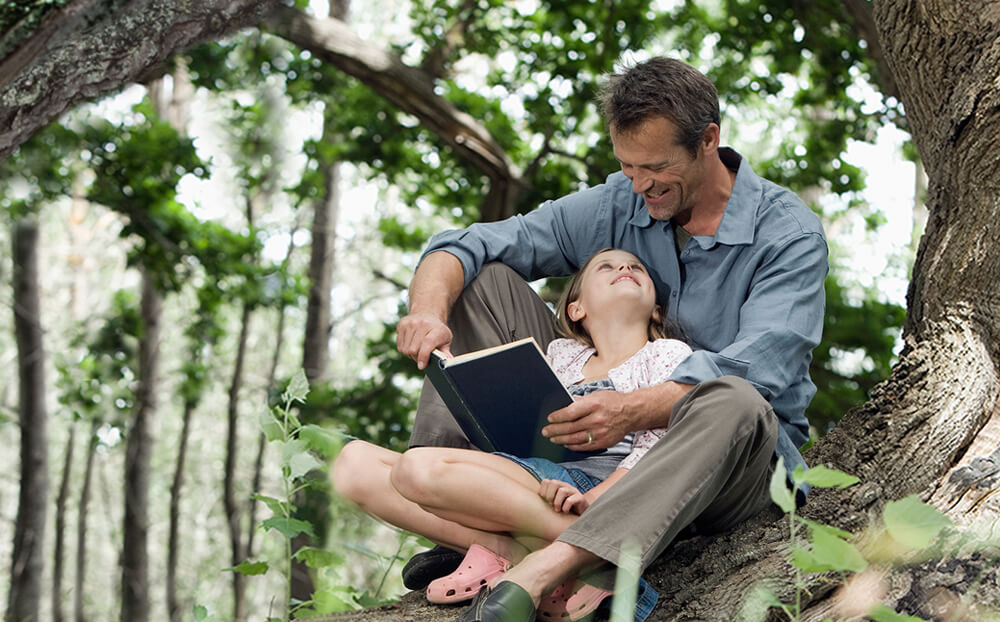 Father and daughter read under a large tree.